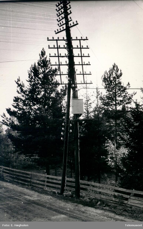 Stolpekryss med med 12 traverser og isolatorer nedover stolpen på kursen Romedal-Valset ved idrettsplassen.
