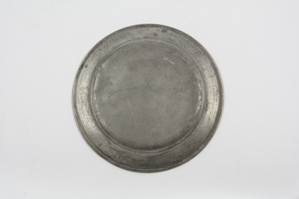 Flat, tinn, sirkelrund, hanken litt skrå med gravert linje ved randen. Baksiden stemplet. Bokstaver risset inn på baksiden av tallerkenens kant.