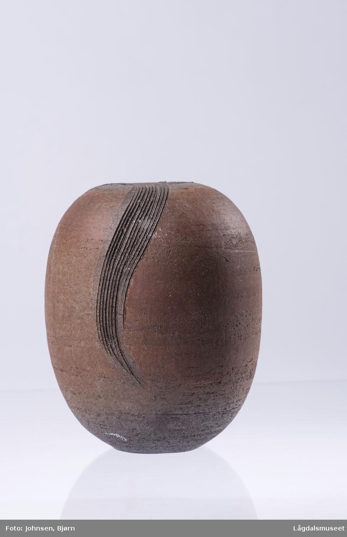 Tre bølger som er risset nedover vasen med utgangspunkt i åpningen er vasens dekor.