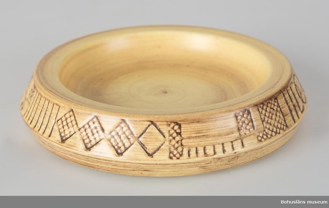 """Rund. Gul matt glasyr. Glasyren skiftar i brunt. Brun dekor på kanten. Under står det """"SYCO 1417 Made in Sweden"""" samt en signatur."""