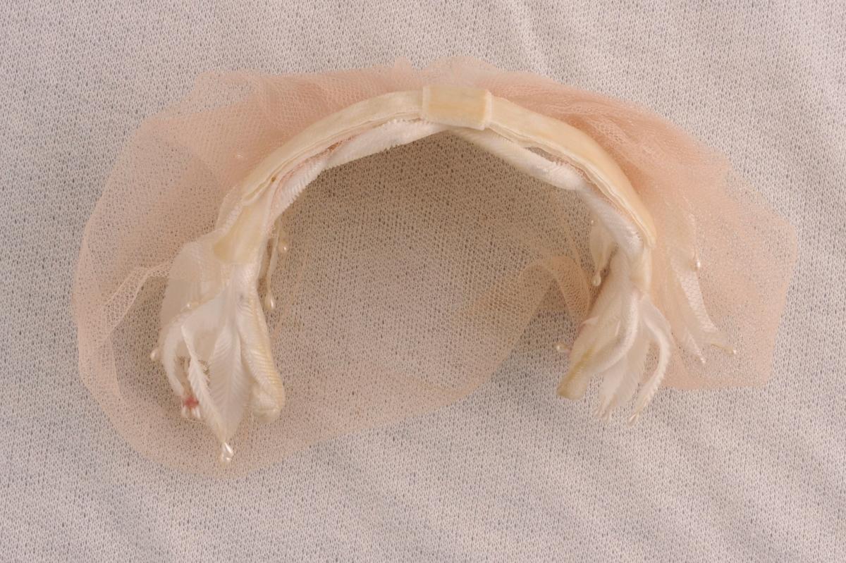 Hårbøyle,sett saman av tre spiler truleg av plast, trekt med nylon,flettemønster.Fjørforma nylonstoff bitar er festa til bøyla, desse har ei dråpeforma perle i enden. Over dette er det fesa eit slør i tyll. I frammkanten av bøyla er det festa eit naturkvitt fløyelsband med sløyfe.