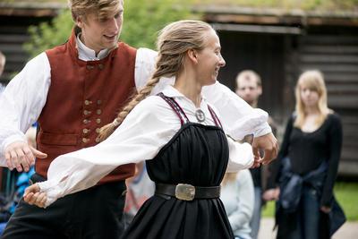 Man and woman folkdansing wearing folk dress