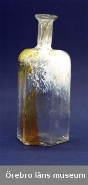 Sexkantig glasflaska i vitt och guldgult. Åsa Brandt har blåst den själv. Märta Hamilton har köpt den av Åsa Brandt 1981. Flaskan ingår i en gåva som museet fick i testamente av Märta Hamiltons dödsbogenom Anne M-L von Schoting.