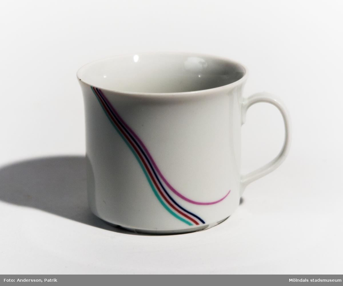 En kaffekopp med öra. Modellen kallas Rainbow och är designad av B Vallien. Tillverkad av Rörstrands under 1980-talet. Grundfärgen är vit och snett över koppen, nerifrån och upp, löper fyra smala, parallella slingor bestående av färgerna grön, röd, mörkblå och rosa. Den sista rosa är formad som en sväng bort från de andra slingorna.