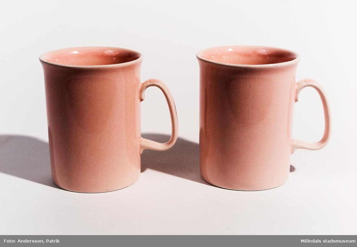 Två rosa muggar med öron, tillverkade under 1980-talet. I botten står MADE IN ENGLAND. Materialet är i porslin med rosa glasyr.