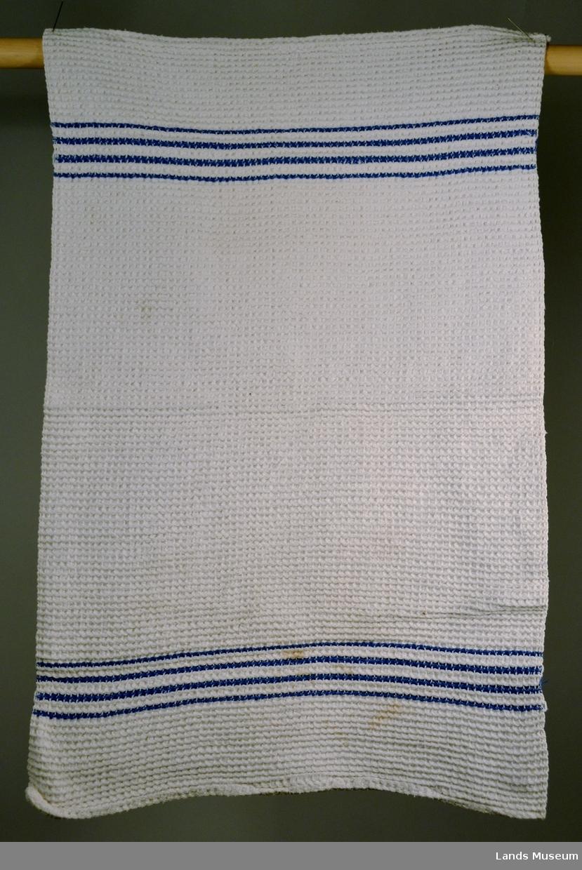 Håndkle til håndvask, hjemmevevet. Fire blå striper i hver ende. Hvitt vaffelmønster.