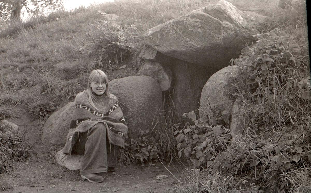 """Birgitta Marnung vid gånggriften i Gillhög.  Gånggriften är en megalitgrav. Megalitgravar (av grekiska mega, stor, och lithos, sten) eller storstensgravar är en serie typer som i Sverige endast anläggs under stenåldern, från c:a 3600-2900 f.Kr. Gånggriften består av stora stenblock, vilka är ställda så att de bildar en gravkammare och en tvärställd gång som leder in till kammaren. Sett uppifrån bildar kammare och gång ett """"T"""". Gravkammaren omges ofta av en hög, som dock relativt ofta är låg och bara runt 1/3 av kammarens höjd som invändigt ofta är närmare 2 meter eller mer. Gånggrifterna ersatte dösarna och byggdes runt 3350-3200 f.Kr. varefter de användes under några sekler, men fynd har visat att man spontant eller periodvis ofta har använt gravkamrarna under senneolitikum och stenålderns slut vilket är detsamma som hällkistornas tid. Därtill har man sporadiskt gjort begravningar i högen eller i kammaren samt dess gång ända fram till järnåldern. I främst kammaren har man hittat obrända skelettdelar och en del enklare föremål från den primära perioden som sträcker sig till c:a 2900 f.Kr. samt spridda fynd från efterföljande perioder.  Källa Wikipedia."""