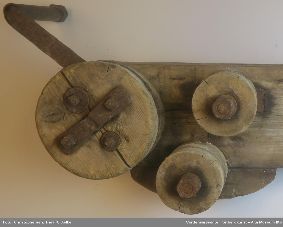 Planke med to små hjul, en sveiv av jern, og et større hju. med foring av jernplater. Dobbel planke for hjul og sveiv.