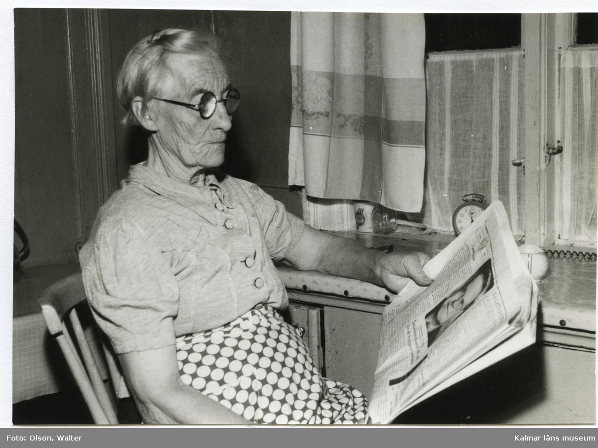 Kvinna som sitter i köket och läser tidningen.