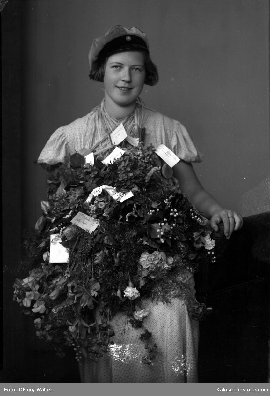 Ateljébild på en kvinna som har tagit realexamen. Enligt Walter Olsons journal är bilden beställd av Birgit Johnsson ifrån Påryd som den också föreställer.