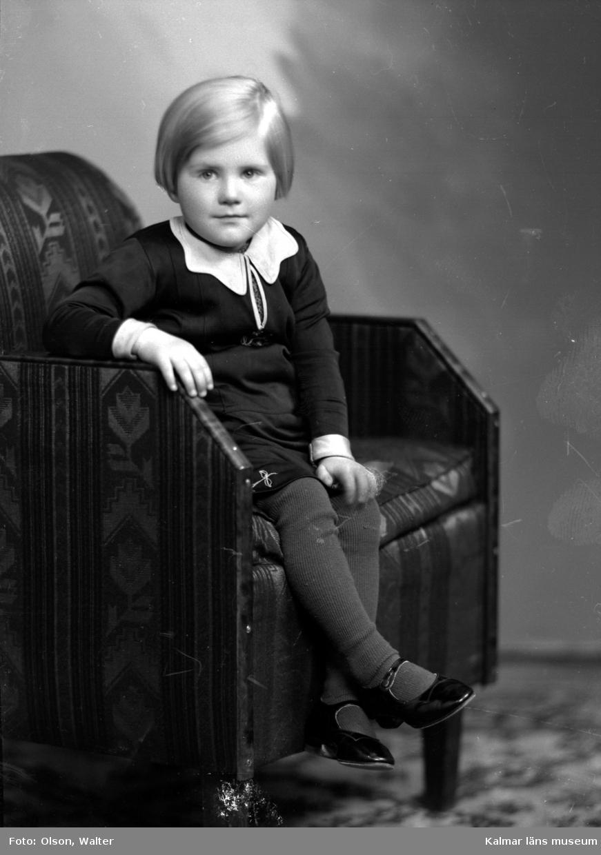 Ateljéfoto. Litet barn sittande i fåtölj.