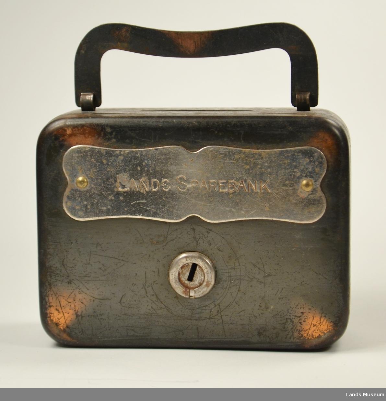 Forma som ein koffert med handtak. Låsbart lokk og påmontert sølvfarga skilt med banken namn på framside.