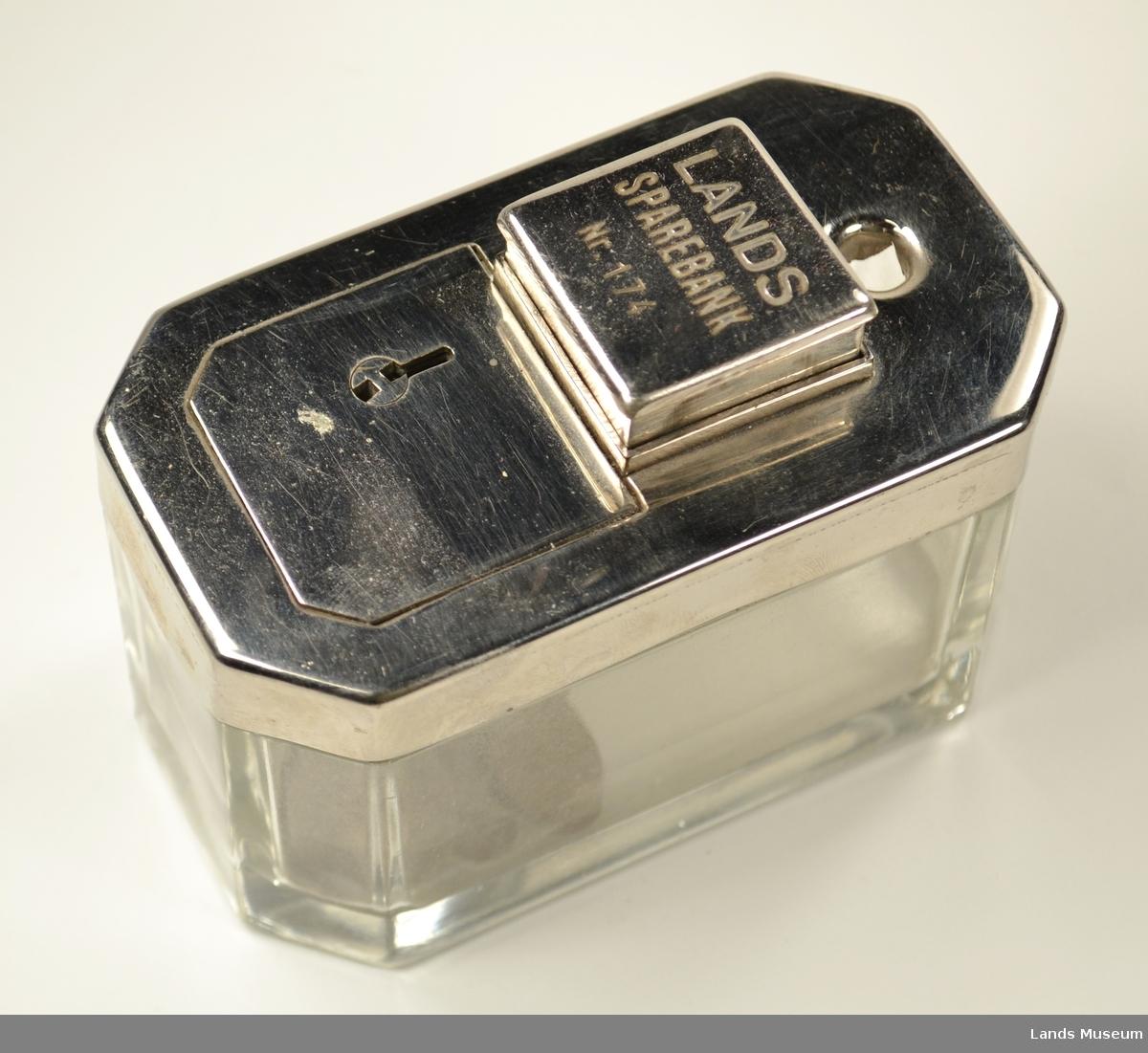 """8 kanta kiste i glass og metall. Låsbar opning på toppen. Hull for sedler. Mynter puttes inn i ein firkanta """"knapp"""". Når ein trykker ned knappen havne mynten ned i glassbeholderen"""