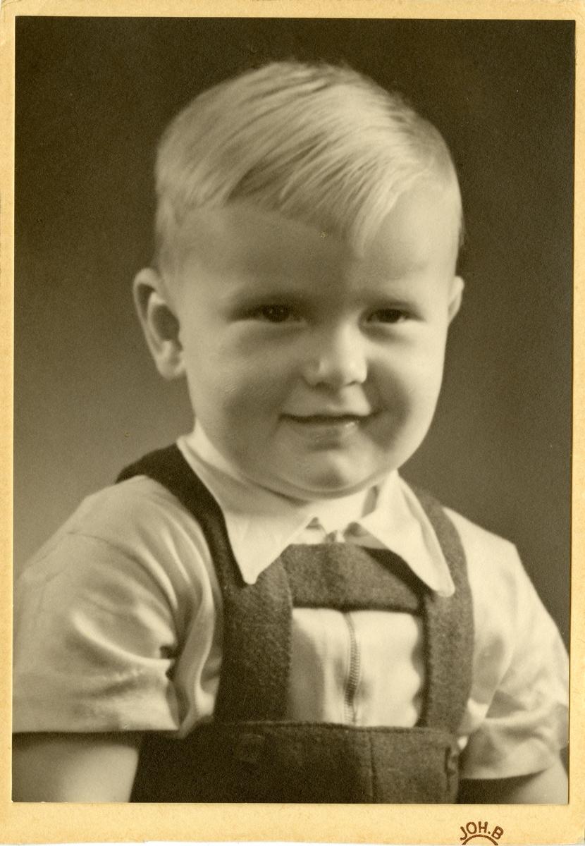 Portrett av en liten gutt. Gutten er iført skjorte og bukse med bukseseler.
