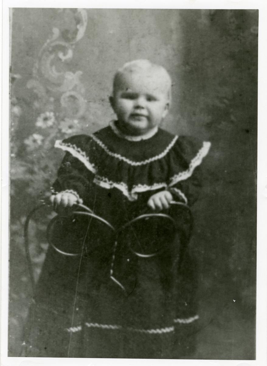 Portrett av en liten gutt. Gutten er iført kjole og står på en stol.
