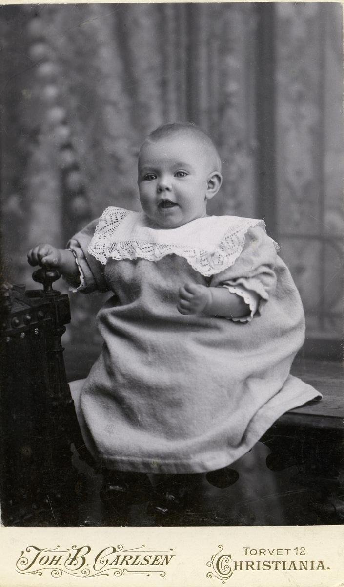 Portrett av en liten baby. Babyen er iført hvit kjole med en hvit krage.