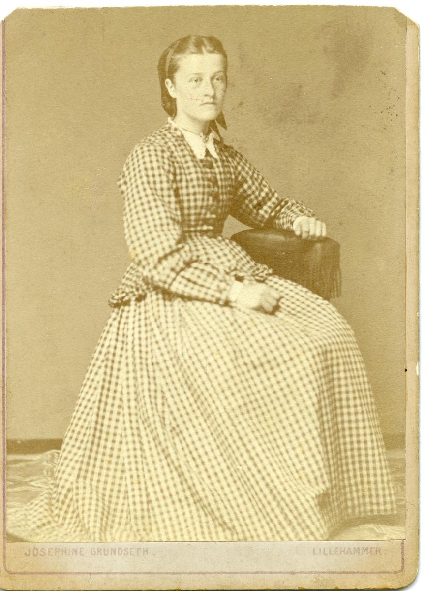 Portrett av en kvinne sittende på en stol. Kvinnen er iført en rutete kjole.
