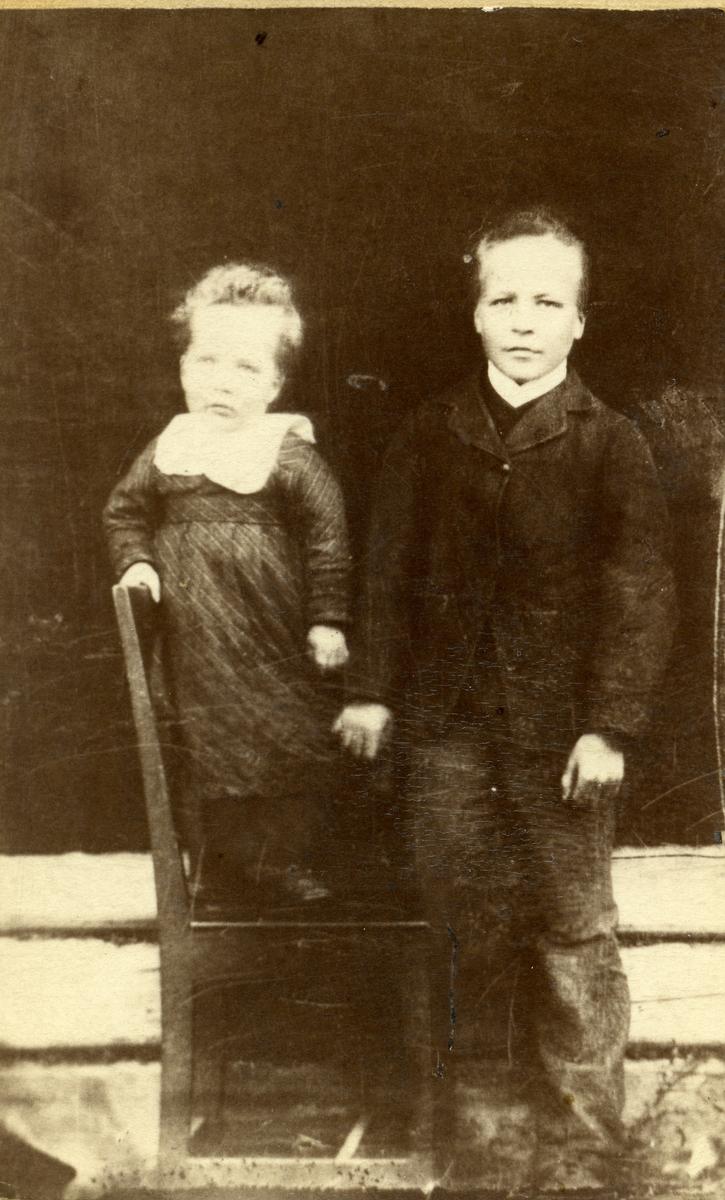 Portrett av en jente og en gutt. Jenta står på en stol og hun er iført en kjole. Gutten er iført jakke og bukse.
