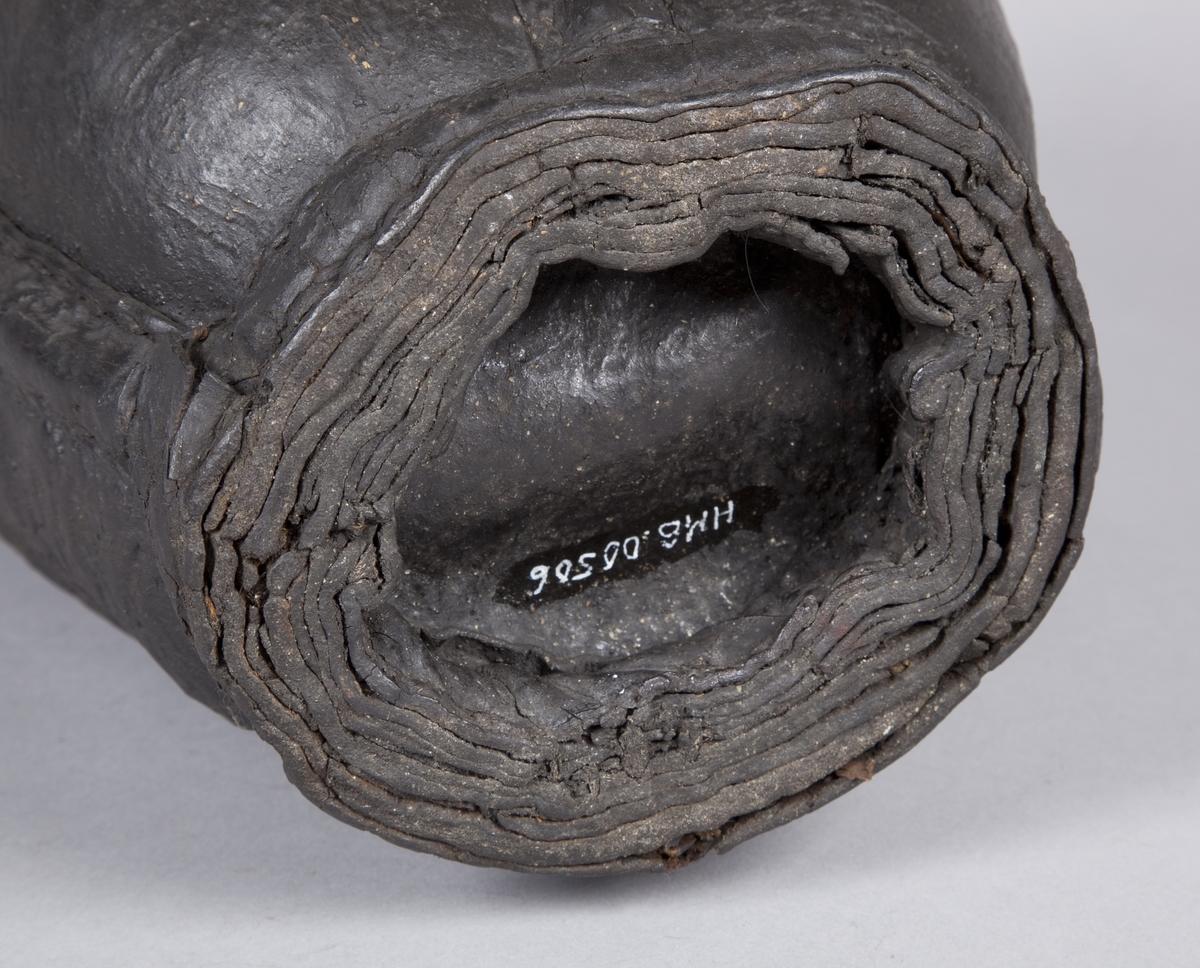 Oval. Satt sammen av 4 lærdeler med sømmer imellom. Bøtten smalner nedover mot bunnen. Bøtten har en hank av tauverk festet i hemper i toppen. Hanken er ødelagt.