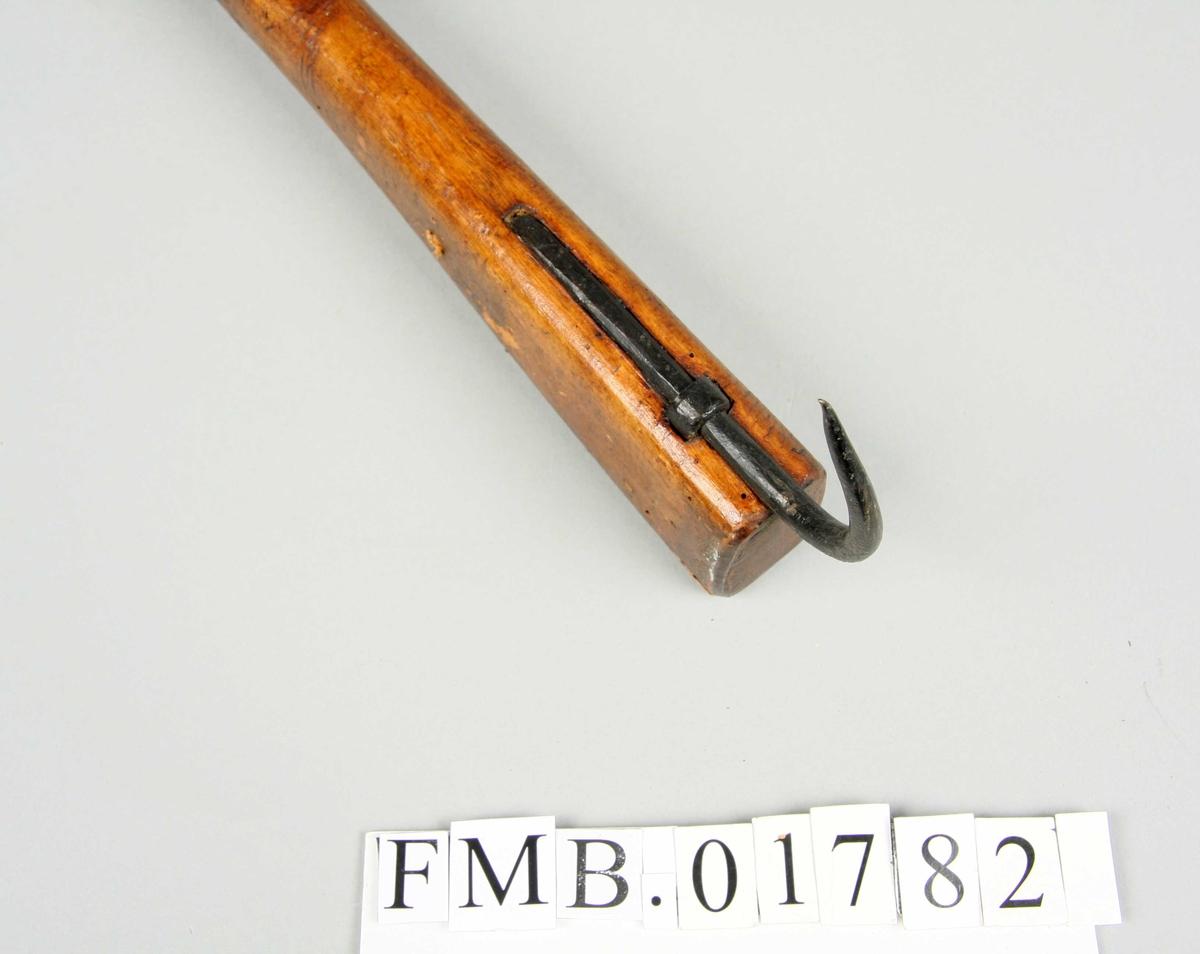 Klepp med langt skaft som smalner i enden mot en flat ende hvor det er skåret et hakk i.