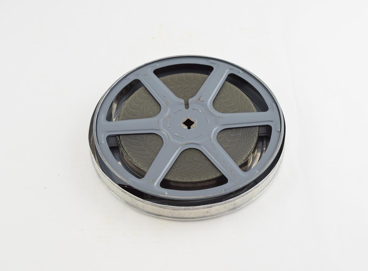 Filmrull i eske. Film på metallspole. Rundt metall etui i to løse deler: bunn og lokk.