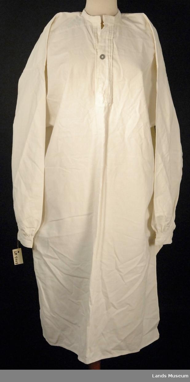 Skjorten har to biser den ene siden av halssplitten, tre biser på den andre. En knapp og et knapphull  i stolpen. Tre knapphull for feste av snipp i halslinningen.  Ermet er rynket mot håndledd. To knapphull for løs mansjettknapp.