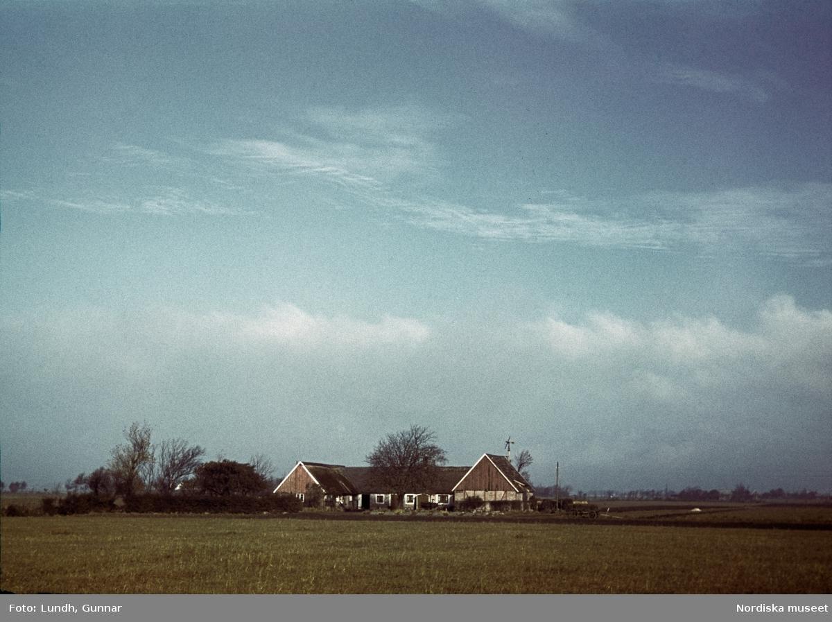En gård, på långt håll omgiven av fält. En vagn står utanför.