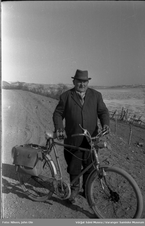 Ole Oksehode (Borr-Ovla) med sykkel. Bildet er tatt rett nedenfor tidligere Amtmannsgammen museum i Varangerbotn, Varangerfjorden i bakgrunnen. April 1967.