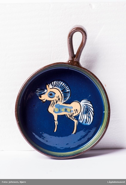 Pannen er dekorert med et motiv av en gul hest i begitning.