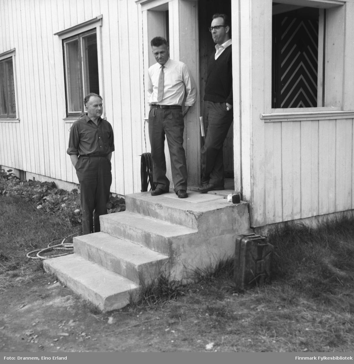 Tre menn står foran et bygg. Sted og mannsnavn er ukjent.