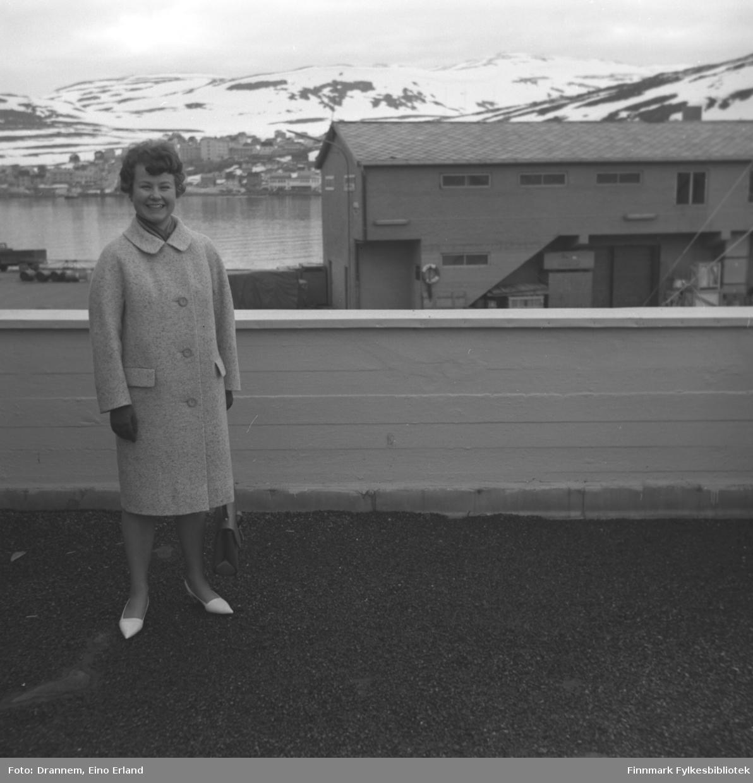 Turid Karikoski på verandataket til Tollboden i Hammerfest. I bakgrunnen ses bydelen Fuglenes under Storfjellet.