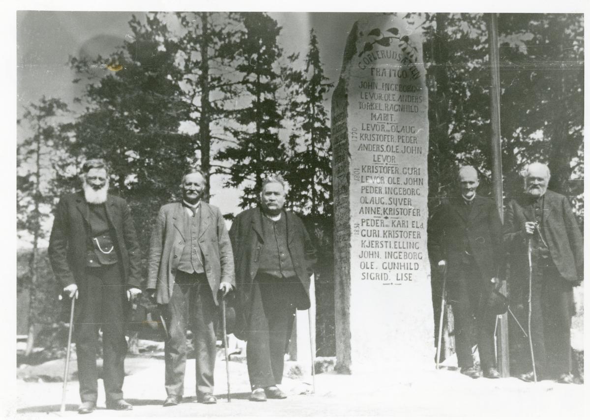 Portrett av medlemmer av Eldsrudfamilien foran minnesbautaen over Goplerudfamilien, Hedalen i Valdres.