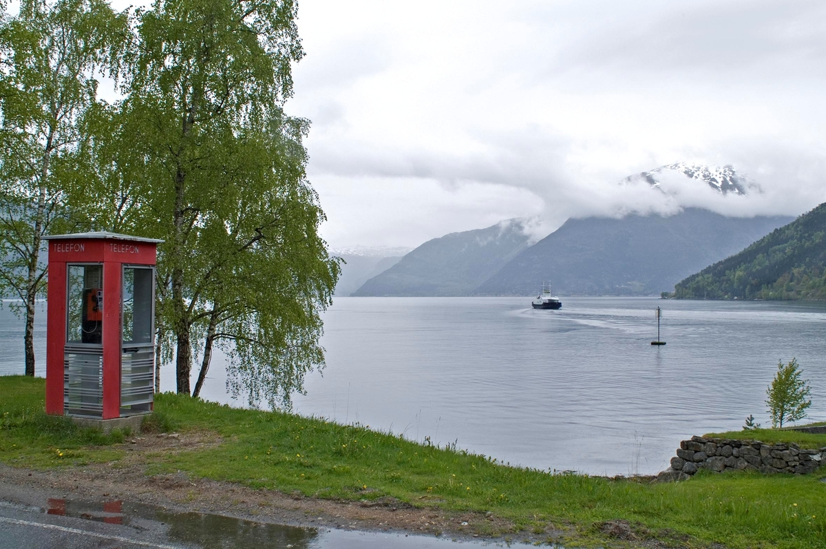 Telefonkiosken står ved Kinsarvik fergekai, og er en av de 100 vernede telefonkioskene i Norge. De røde telefonkioskene ble laget av hovedverkstedet til Telenor (Telegrafverket, Televerket). Målene er så å si uforandret.  Vi har dessverre ikke hatt kapasitet til å gjøre grundige mål av hver enkelt kiosk som er vernet.  Blant annet er vekten og høyden på døra endret fra tegningene til hovedverkstedet fra 1933. Målene fra 1933 var: Høyde 2500 mm + sokkel på ca 70 mm Grunnflate 1000x1000 mm. Vekt 850 kg. Mange av oss har minner knyttet til den lille røde bygningen. Historien om telefonkiosken er på mange måter historien om oss.  Derfor ble 100 av de røde telefonkioskene rundt om i landet vernet i 1997. Dette er en av dem.