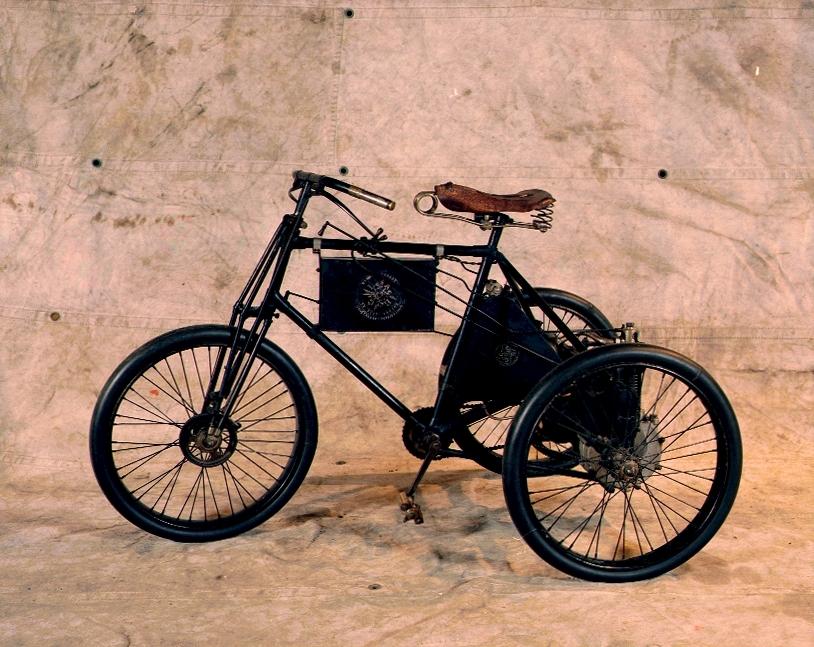 """Trehjulig motorcykel med motorn placerad mellan bakhjulen. Kraften överförs från motorn till bakaxeln med kugghjul. Bandbroms på bakaxelns differential och på framhjulets nav. Cudell & Cie, Aachen ytförgasare. Batteritändning till tändstift, torrcellbatteriet i lådan på det horisontella ramröret. Reglaget vid styret är handtag till fram och bakbroms. Reglage vid ramen till luftintag på tanken (2 st).  Museets exemplar har haft en smidd """"ögla"""" för påhängsvagn.  Encylindrig luftkyld fyrtakts bensinmotor, cylindervolym 239 cc, cylinderdiameter 62 mm Slaglängd 70 mm 1 ¾ hk vid 1500 varv/minut Högsta fart cirka 45 km/tim Hastighetsreglering genom tändningen. Motorns vikt:  18 kg."""