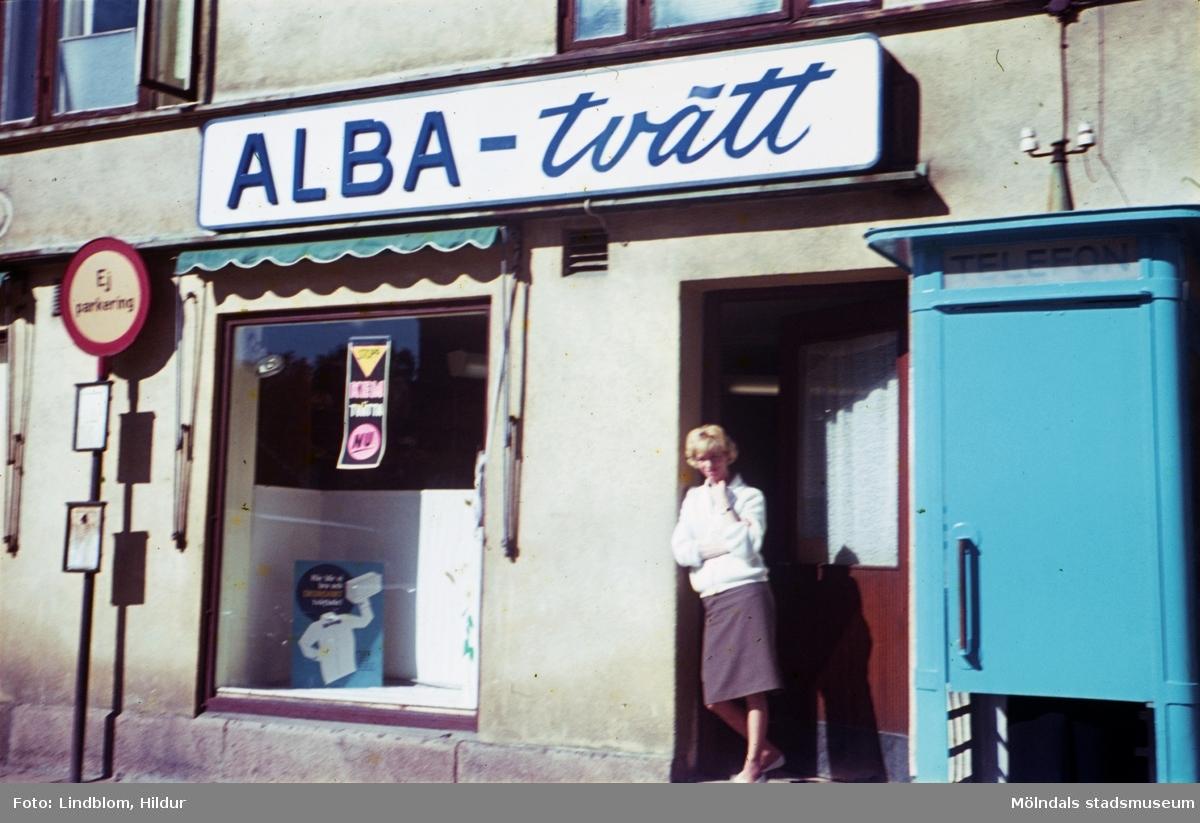 En kvinna står i dörren till tvätteriet ALBA-tvätt med adress Kvarnbygatan 43 vid Gamla Torget i Mölndal, 1960-tal. Till höger ses även en blå telefonkiosk.  För mer information om bilden se under tilläggsinformation.