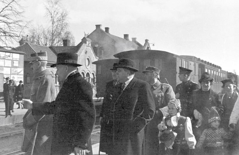 Hambro, fylkesmann Knut Nordanger og politimester Reidar Beichmann tar imot kongefamilien på Hamar stasjon. Foto: Fotograf Normann/Domkirkeoddens fotoarkiv.