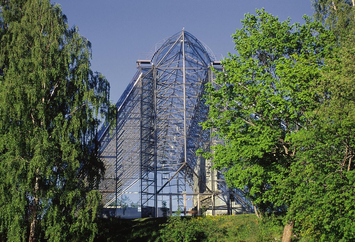 Vestfasaden av vernebygget over domkirkeruinen, delvis skjult bak grønn trær. (Foto/Photo)