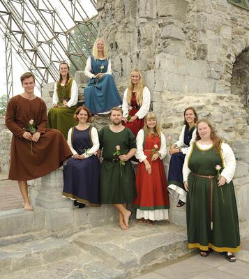 Ni ungdommer i middelalderantrekk poserer med hver sin rose i domkirkeruinene.