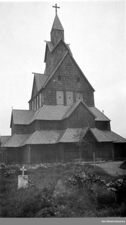 """På bildet ser vi Heddal Kirke slik den stod etter arkitekt Johan Heinrich Nebelongs restaurering i årene 1849-1851. Dette kommer det frem ved at vi ser 3-4 store vinduer på 3 av sidene i """";3 etasje"""";. Disse ble senere fjernet og erstattet med """";glugger"""";, da ønsket om en gjenrestaurering materialiserte seg for alvor i mellomkrigstiden. Ikke en flis av Nebelongs arbeid overlevde den siste restaureringen, som ble avsluttet i 1955. Kilde: Leif Anker og Jiri Havrans """";De Norske Stavkirkene, ARFO 2005 (ISBN 82-91399-27-1) Side 172 - 174."""