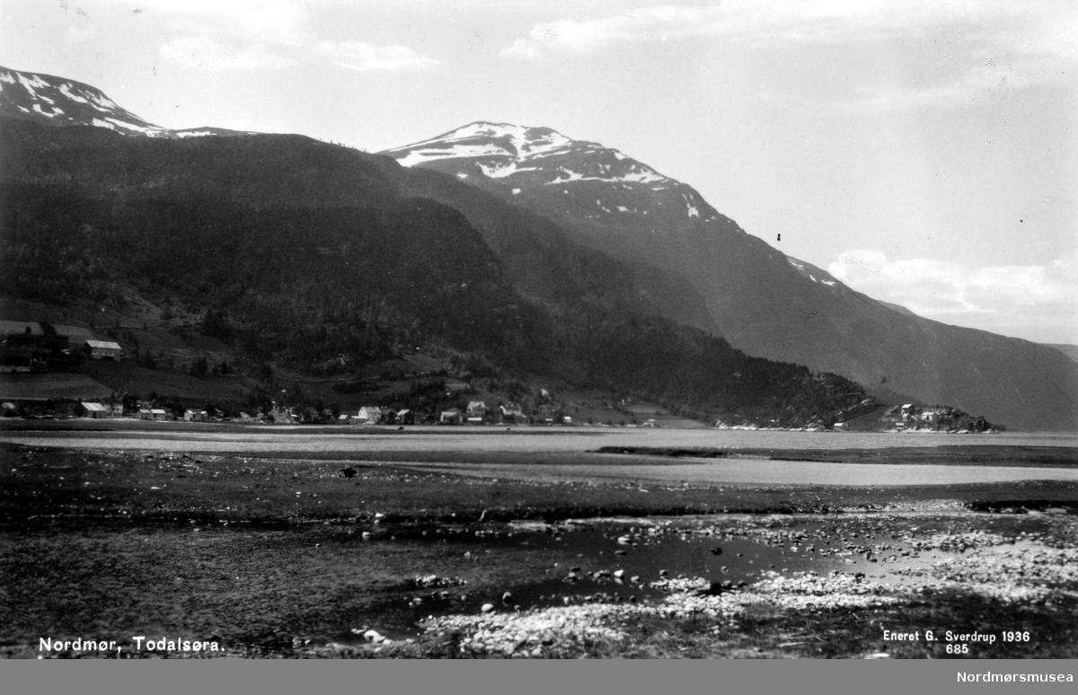 "Postkort: "";Nordmør, Todalsøra. Eneret G. Sverdrup 1936. 685""; Foto fra Todalsøra i Surnadal kommune, hvor vi ser fra fjorden i forgrunnen og bygda i bakgrunnen. Fra Nordmøre Museums fotosamlinger."