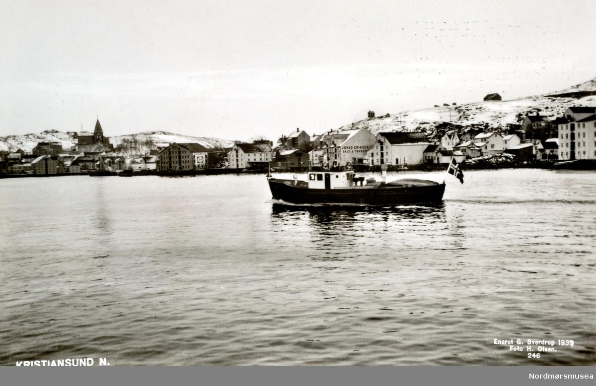 """Postkort med tekst:  """"Kristiansund N"""" Vi ser brannsprøyta """"Slukk II"""" som kommer inn Sørsundet mot havna og har Innlandet og Hønebukta på høyre side.  I bakgrunnen Nordlandet med Nordlandet kirke.  (Fra Nordmøre Museums fotosamlinger.)"""