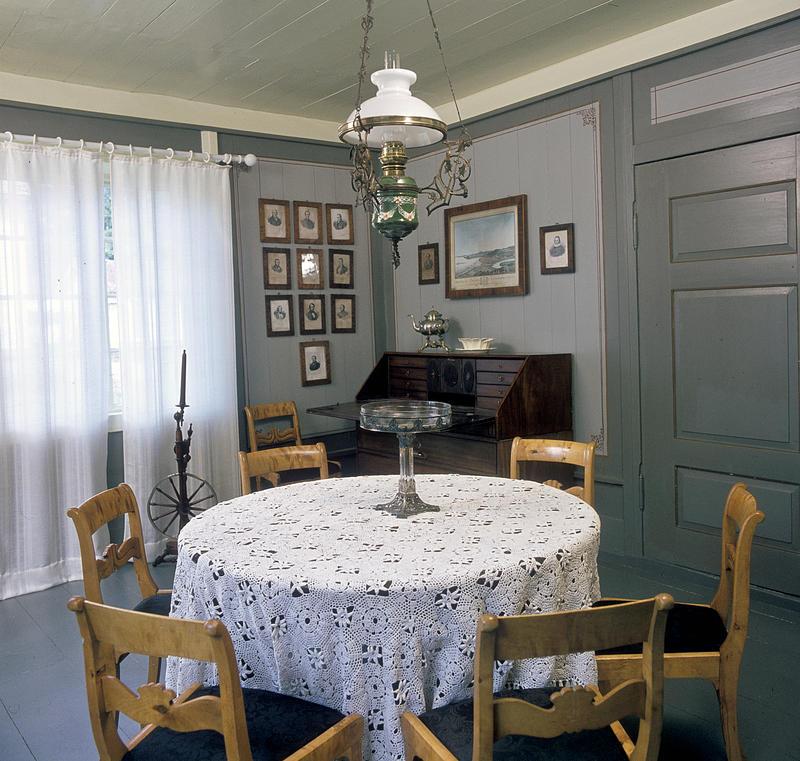 Interiør; rundt bord med hvit duk og stoler rundt i forgrunnen, husordel, mange fotografier på veggen og en oljelampe over bordet. (Foto/Photo)