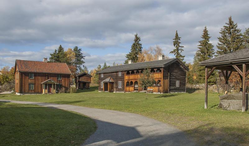 Grusveg som fører over et tun med en låve lengst til høyre, samt to brunlige tømmerbygninger hvorav det ene med svalgang.