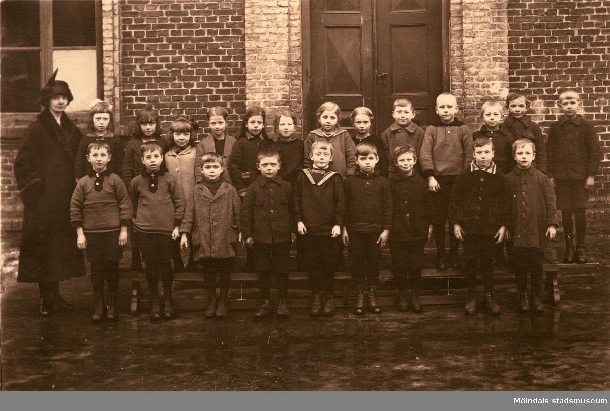 Lärarinnan Agda Carlson med småskoleklass vid Grevedämmets skola i Mölndal på 1920-talet.  För mer information om bilden se under tilläggsinformation.