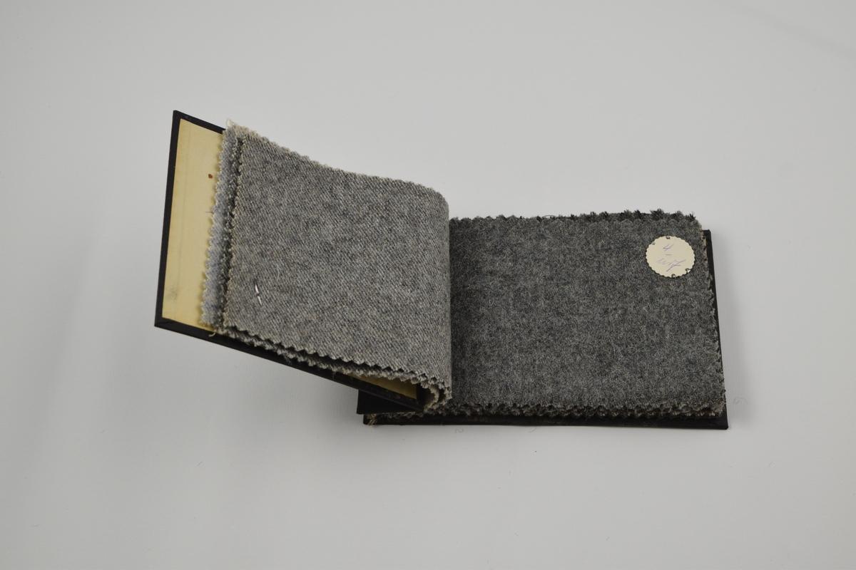 Prøvebok med 12 prøver. Middels tykke ullstoff, ensfargede eller med striper, ett smårutet. Alle stoffer er merket med en rund papirlapp festet med metallstifter hvor nummer er påskrevet for hånd.  Stoff nr. 1/ull (lys blå), 2/ull (lys grå), 3/uif (lys grå), 4/uif (grå), 5/uif (grå med striper), 6/uif (grå-brun), 8/ull (lys blå med sorte striper), 9/ull (lys blå), 10/ull (blå-grå, smårutet), 11/ull (grå-brun), 12/ull (grå-brun), 13/ull (grå).