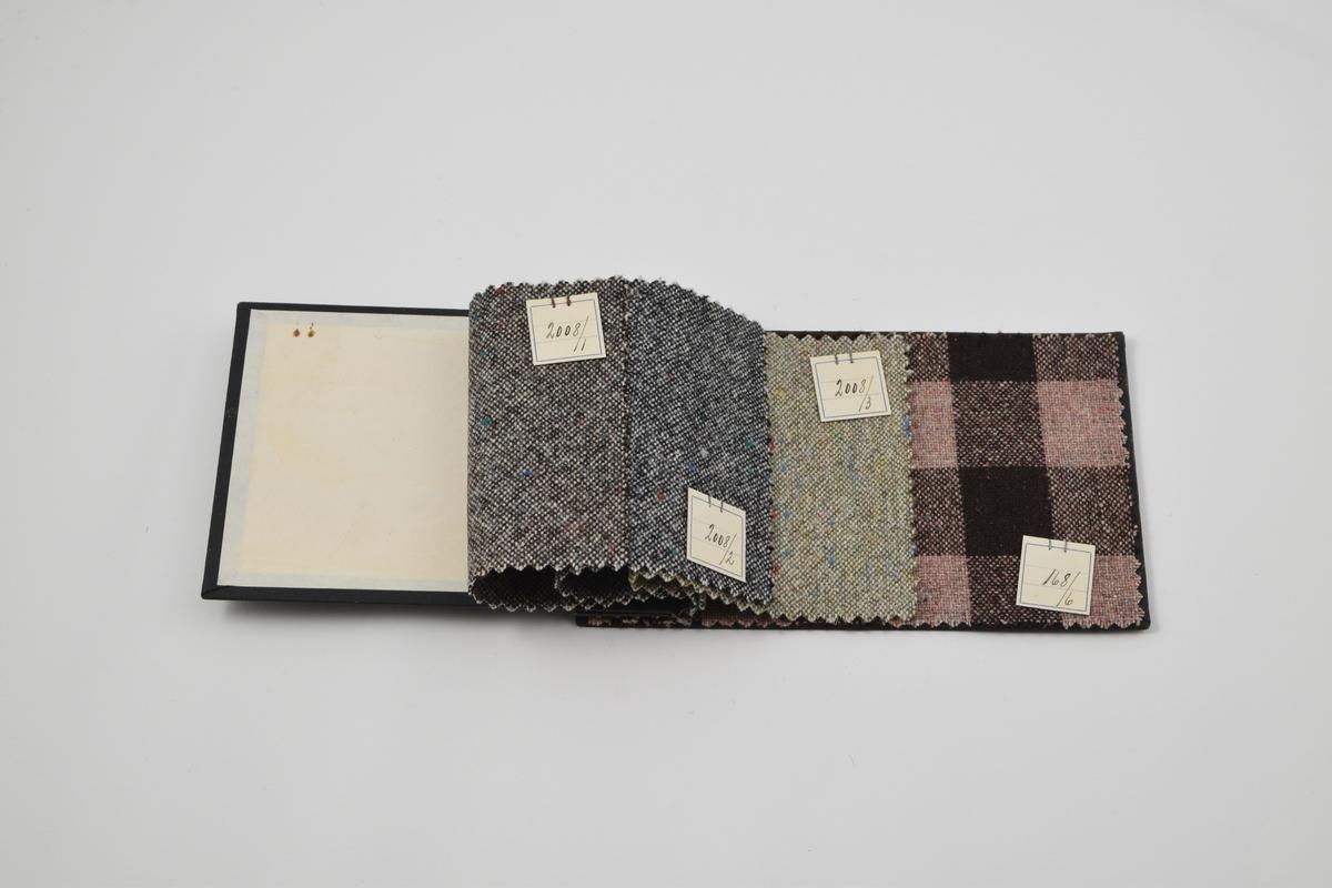 Prøvebok med 4 prøver. Middels tykke ullstoff med tilfeldigplasserte prikker i ulike farger, samt ett rutet stoff. Alle stoffer er merket med en firkantet papirlapp festet med metallstifter hvor nummer er påskrevet for hånd.   Stoff nr. 2008/1 (brun), 2008/2 (grå), 2008/3 (lys grønn), 168/6 (rosa og brun ruter)