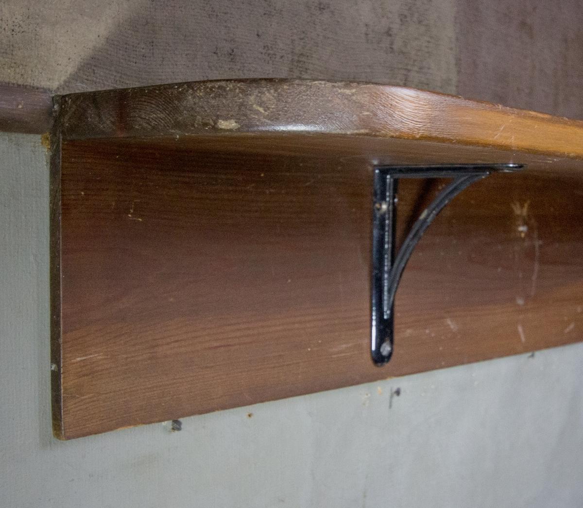 Hylla, vägghylla, av brunbetsad furu. Slätt hyllplan med ett rundat hörn. Horisontell bräda fäst på baksidan med tre svartmålade metallkonsoler som håller upp hyllplanet.