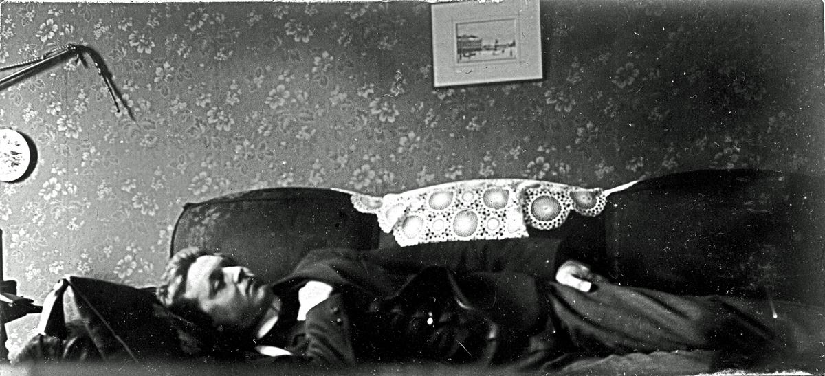 En man som ligger på en soffa. Fotograf Alfred Bergendahl. Givare H Bergendahl.