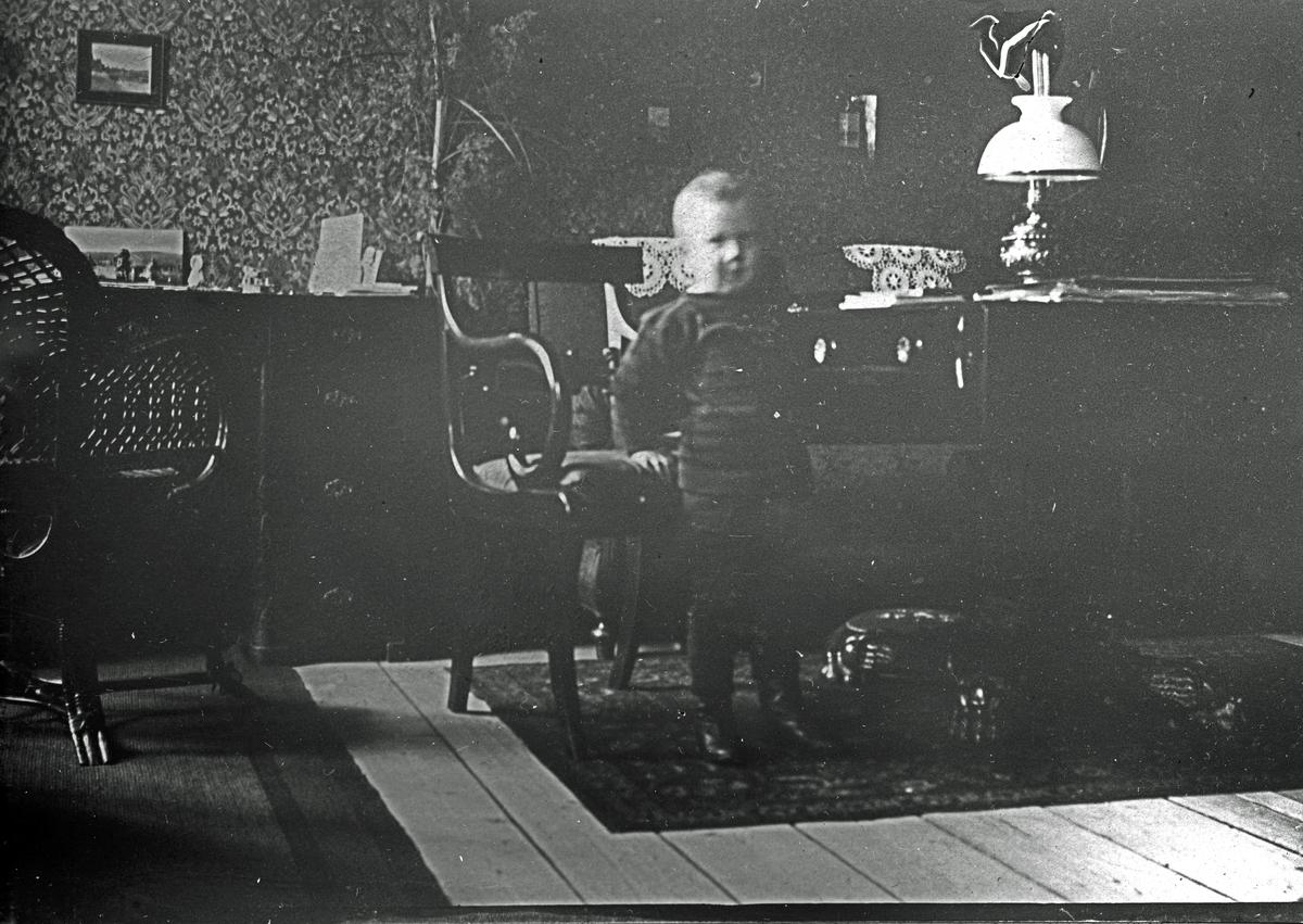 Ett barn bredvid en stol och ett bord. Fotograf Alfred Bergendahl. Givare H Bergendahl.