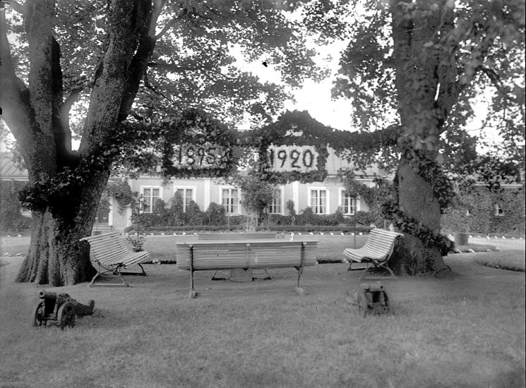 """En vy mellan två ekträd, och några parksofformed några små salutkanoner framför.Mellan träden hänger ett slags girlander med årtalen """"1895""""och """"1920"""".I bakgrunden skymtar huvudbyggnaden på Gårdsby."""